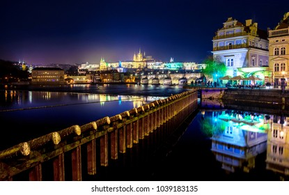 Cityscape of Prague with Charles bridge, medieval towers and colorful buildings at night, Czech Republic