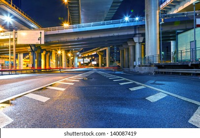 cityscape with road overpass in the lamplight with reflections on the asphalt