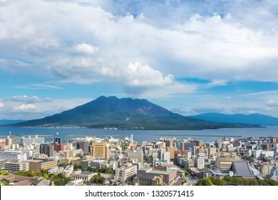 Cityscape with Sakurajima mountain, sea and blue sky background view from Shiroyama Park Observation park, Kagoshima, Kyushu, Japan