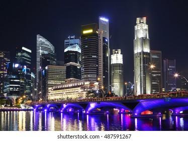 Cityscape of Singapore illuminated at night with Esplanade bridge in foreground