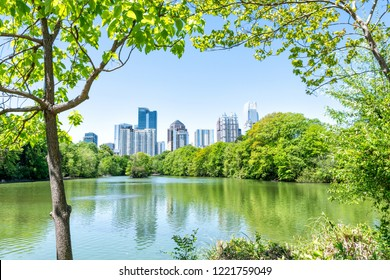 Cityscape, skyline of Atlanta, Georgia in Piedmont Park, looking, framing through trees, scenic water, urban city skyscrapers downtown at Lake Clara Meer