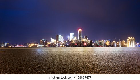cityscape and skyline of chongqing at night on view from empty asphalt road