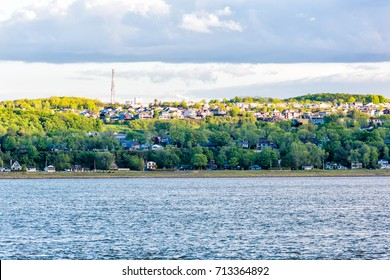 Cityscape skyline of Levis, Quebec, Canada during sunset with many houses on shore with water waves