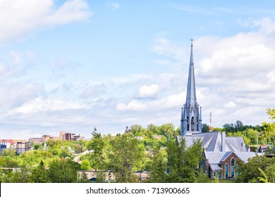Cityscape or skyline of Saguenay, Canada city in Quebec in summer with church spire, many houses, buildings and green park trees
