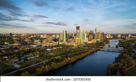 Cityscape Skyline View Austin , Texas , USA aerial drone view amazing sunset golden hour as sun casts gold colors across downtown capital city Town Lake and bridges crossing Colorado river