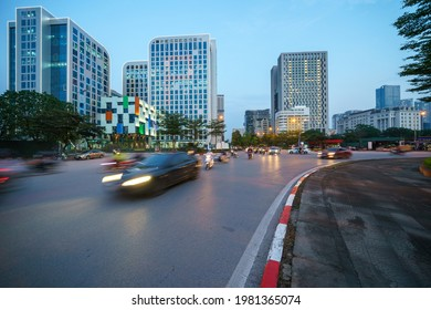 Cityscape of a street in Hanoi with high buildings during sunset time with blurred cars running on street