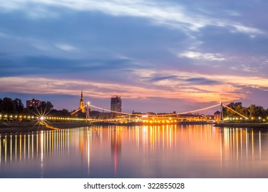 Cityscape at sunset over a river, with city lights and lit bridge and water reflections. Osijek, Croatia
