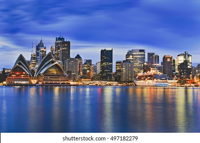 Cityscape of Sydney city CBD across Harbour at sunrise reflecting bright lights of skyscrapers and major landmark in still blurred waters under clouds.