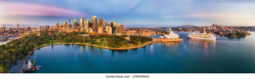 Cityscape of Sydney city CBD with major architectural landmarks on shores of Sydney harbour in early pre sunrise hour in wide aerial panorama.