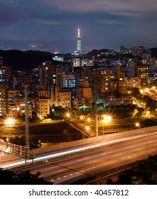 Cityscape of Taipei night with traffic light and bridge.