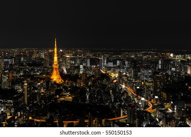 Cityscape of Tokyo at night, as seen from the top of one of the highest buildings in Roppongi Hills, with the illuminated Tokyo Tower glowing in the dark. Long exposure.