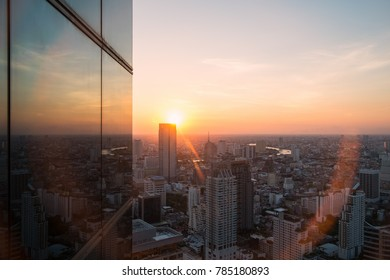 Cityscape from the top of building reflect to sunset with flare