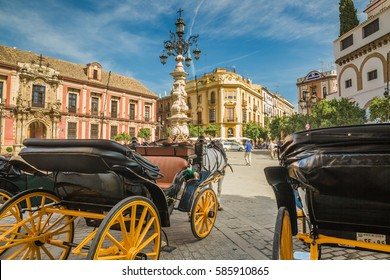 Cityscape. Touristic horse carriages wait for passengers in the streets of Seville in Spain.