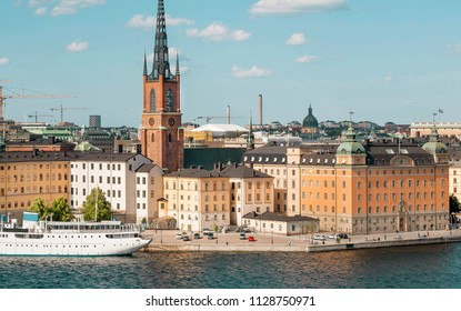 Cityscape with towers of Stockholm, water around and touristic boat on cruise through the islands
