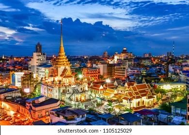 Cityscape twilight of Wat Trimit Witthayaram Worawihan and chinatown yaowarat area in Bangkok, Thailand.