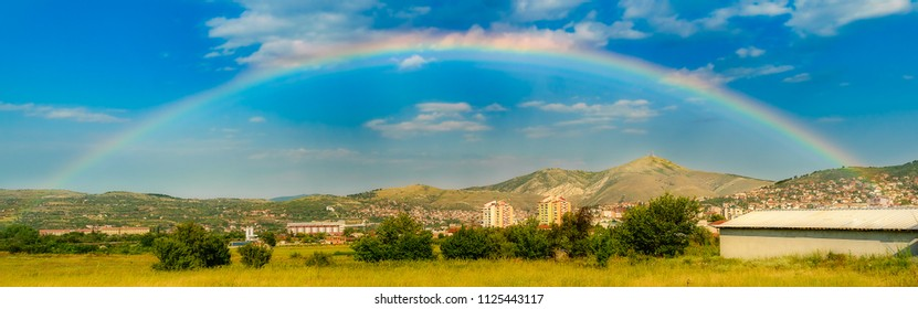 A cityscape under a rainbow on a hot summer afternoon.