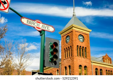Cityscape view of Birch Avenue street sign with clock tower in Flagstaff, Arizona.