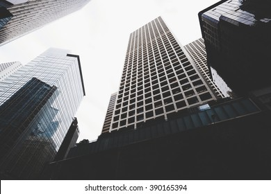 Cityscape view with business buildings with contemporary architecture in metropolitan city in day. High-rise modern skyscrapers in big town against grey sky