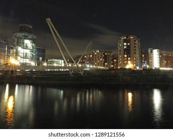 a cityscape view of the canal entrance to the clarence dock area of leeds with a pedestrian bridge crossing the water with reflections of lights and buildings against a night sky with clouds