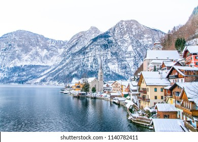 Cityscape view of Hallstattersee lake and mountain in daylight with snow. Panoramic view of famous Hallstatt lakeside town during winter. Town square in Hallstat. Salzkammergut region, Austria. Europe