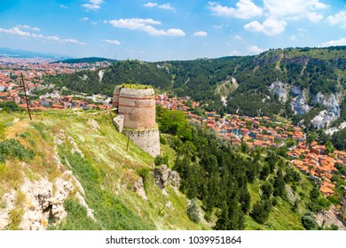 Cityscape view from historical Kutahya Castle with brick stone walls and bastions on cloudy blue sky background in Turkey.