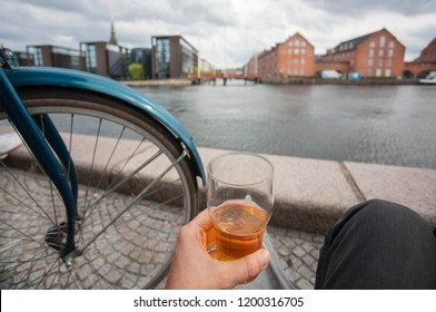Cityscape with water channel, old buildings and relaxed visitor of Copenhagen with beer in hand, Denmark. Danish capital with cycles, old houses and tourists.