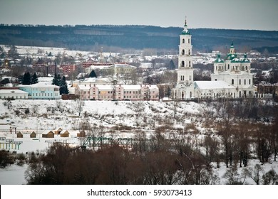 The cityscape of Yelabuga in winter: Shishkin house museum and Spassky cathedral in snowy weather and big forest in the background