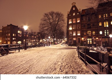 Cityscenic from Amsterdam covered with snow in the Netherlands at night