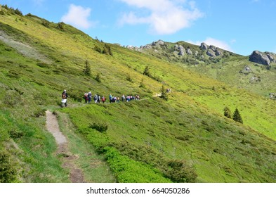 Ciucas Mountain, Romania, June 10, 2017:  Hikers with backpacks walk on mountain path on gorgeous summer day.