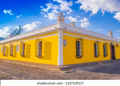 Ciudad de Guatemala, Guatemala, April, 25, 2018: Outdoor view of corner perspective of a bright yellow colonial house with barred windows in Antigua city