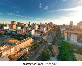 CIUDAD DEL ESTE, PARAGUAY - MAY 22, 2021: People and vehicles cross the Friendship Bridge to make purchases in Ciudad del Este, several shops in the background