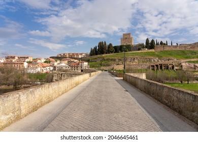 CIUDAD RODRIGO, SPAIN - MARCH 08, 2021: View of the castle and walls of Ciudad Rodrigo since stone bridge, Salamanca, Castilla y León, Spain.