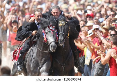 Ciutadella, Minorca / Spain - June 23, 2012:  Riders relatives to each other embrace while galloping surrounded by a cheering crowd during Saint John  traditional celebrations in the Spanish island.