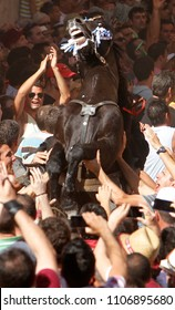 Ciutadella, Minorca / Spain - June 23, 2012:   A horse rears up on his legs surrounded by a cheering crowd during Saint John festivities in Ciutadella in the Spanish Mediterranean island of Minorca
