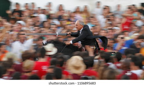 Ciutadella, Minorca / Spain - June 23, 2012: A rider galloping surrounded by a cheering crowd tries to spear on a pending ring during Saint John horse traditional celebrations in the Spanish island.