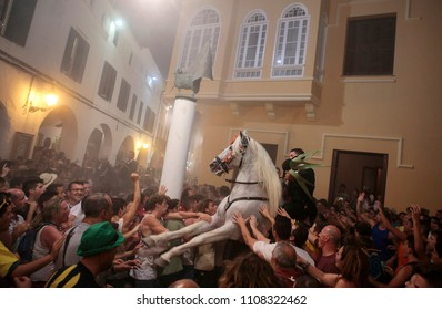 Ciutadella, Minorca / Spain - June 23, 2016: Riders rear up on his horse while surrounded by a cheering crowd during the traditional Saint John horse celebrations in the Spanish island of Minorca