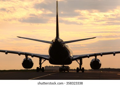 Civil airliner towing with truck at dawn.