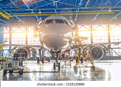 Civil airplane jet on maintenance of engine and fuselage check repair in airport hangar. Bright light at the gate.