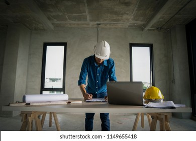 civil architech engineer choose color of building with laptop,engineering and architecture concept.Blue print is fake only for stock photo.
