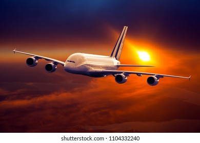 Civil double decker plane in flight. Aircraft flying on a high altitude above the clouds during flaming sunset. Airplane front view.