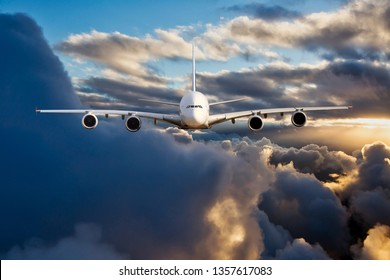 Civil double decker plane in flight. Aircraft flying on a high altitude above the clouds during the sunset. Aircraft front view.