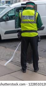 civil enforcement officer traffic warden tries to fix parking meter in busy high street