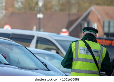 civil enforcement officer or traffic warden writes out parking ticket for vehicle in UK