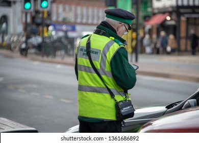 civil enforcement officer or traffic warden with glasses in typical English town