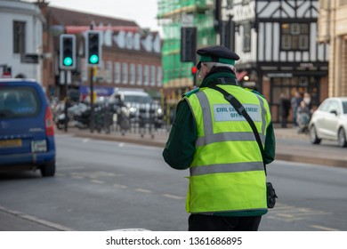 civil enforcement officer or traffic warden walks up the street whilst writing a parking ticket in the UK