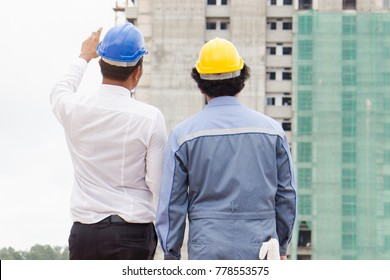 Civil engineer and client discussing project construction period and checking material outside of site construction. Architect contractor in blue helmet pointing at building.
