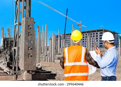 Civil engineer and foreman control working at pile driver works to set precast concrete piles in a construction building area