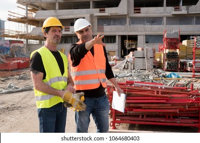 Civil engineer giving instructions to a construction worker. Outdoors