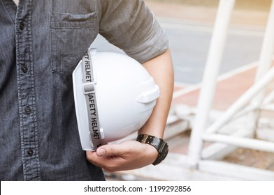 Civil engineer holding white safety helmet and blueprint outside, Asian engineer looking and surveying at a construction site, Safety first