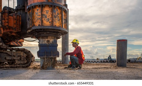 civil engineer inspection construction site concrete pile driving in safety uniform protection